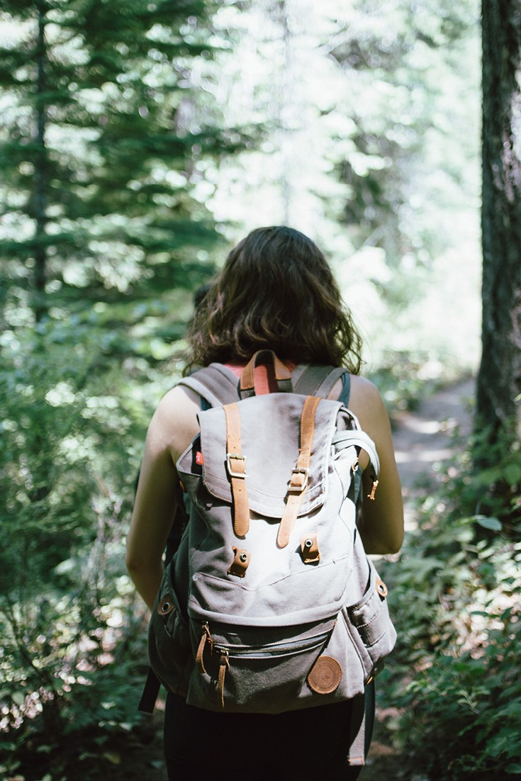Girl in the woods with backpack on