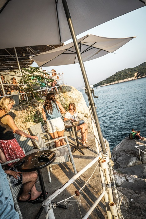 Terraced drinking area at Buza Dubrovnik - Buza Bar is one of Dubrovnik's coolest nightlife spots. This cliffside bar bosts beautiful views of the sea from a hidden spot in Dubrovnik Old Town. One of the top things to do in Dubrovnik! Read now #dubrovnik #travel #wanderlust