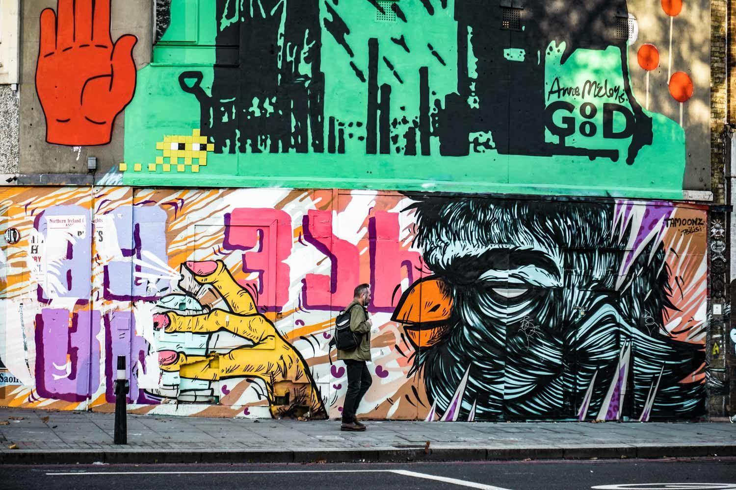 Man walking in front of mural Shoreditch
